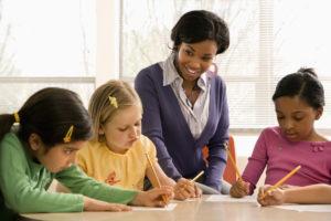 Teacher helping students in school classroom.